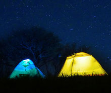 Lit tents against a night sky